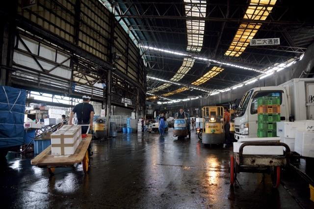 東京築地魚市場。 拍攝手法:建築物的幾何延伸引導視覺,等待工作的攤販走過。